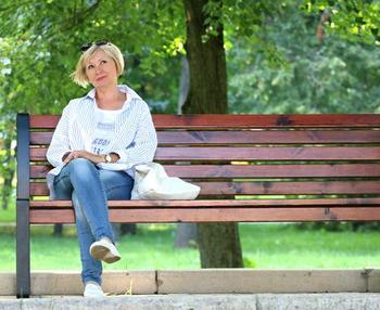 Dame på benk i park