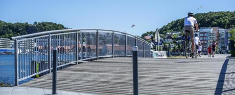 Mann som sykler over bro